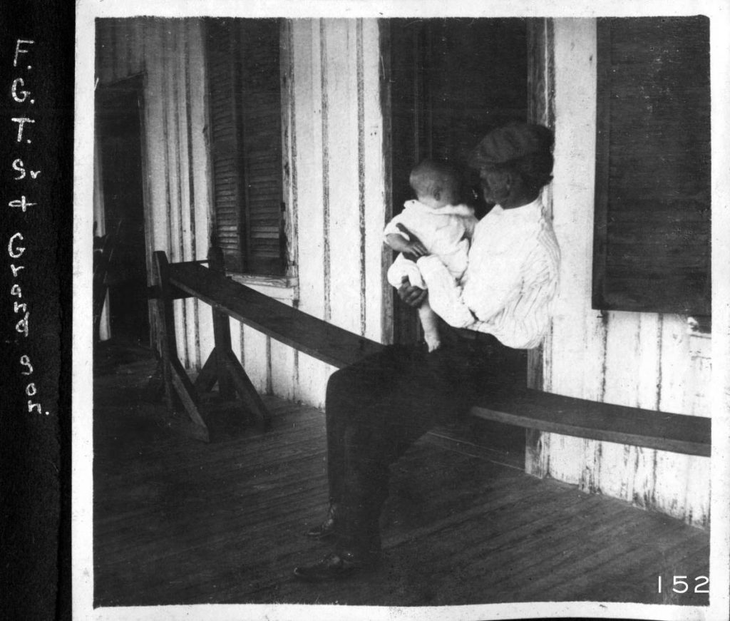Black and white photo of man holding baby on joggling board