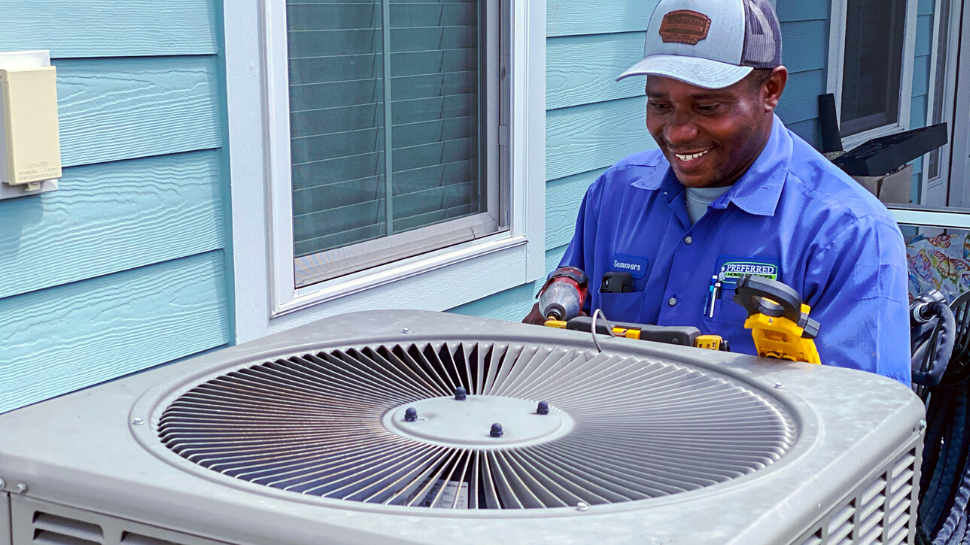 Preferred Home Services technician working on AC unit