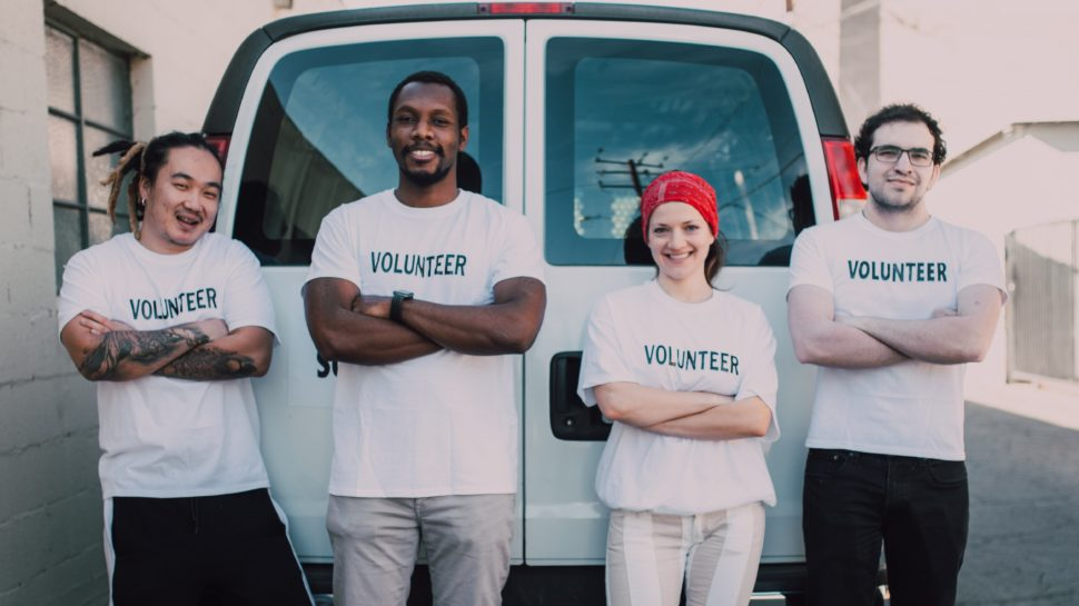 Four volunteers in front of a truck with the word volunteer written on their shirts.