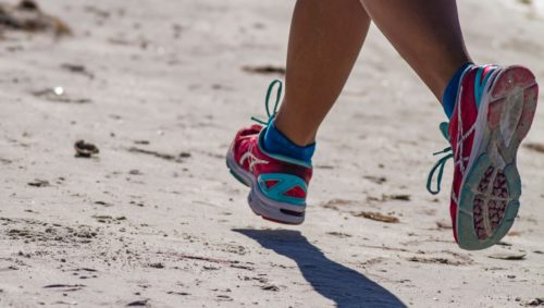 Lower body shot of person in athletic shoes running across sand
